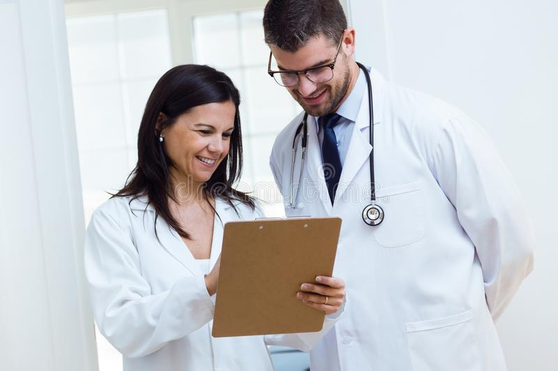 Confident male doctor and his nurse working in the office. stock images