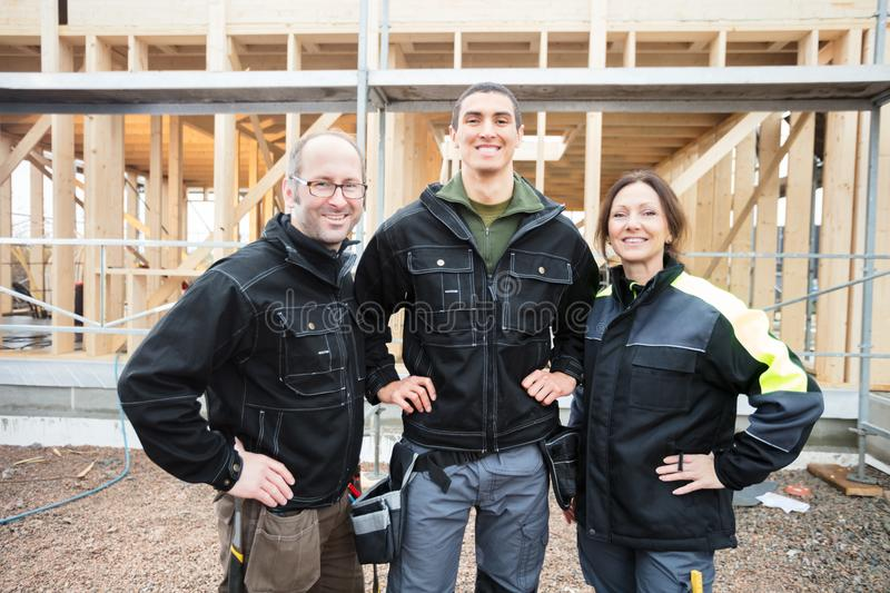 Confident Carpenters Standing Against Incomplete Building. Portrait of confident male and female carpenters standing with hands on hips against incomplete stock photo
