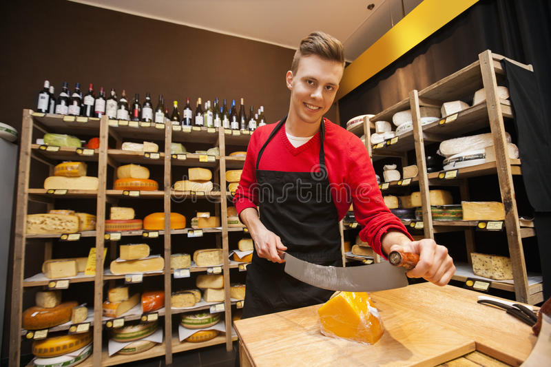 Portrait of confident male salesperson cutting cheese in store royalty free stock image