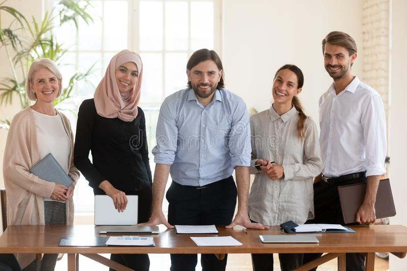 Portrait of confident male team leader with smiling diverse colleagues. royalty free stock photos