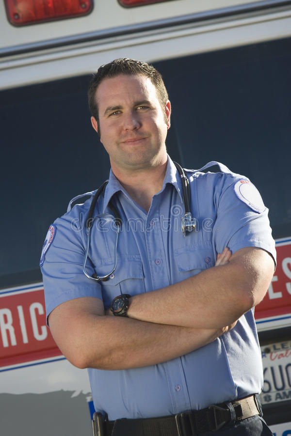 Portrait Of A Confident Middle Aged EMT Doctor. Standing with ambulance in the background royalty free stock photography