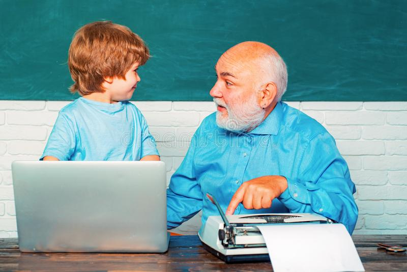 Portrait of confident old male teacher. Teacher helping his teen pupil on education class. Young boy doing his school stock photography