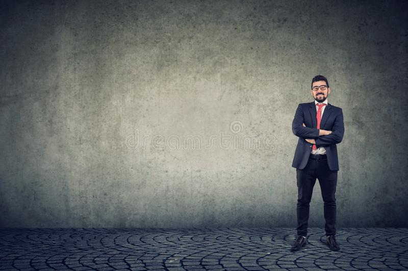 Confident smiling business man standing against a wall background royalty free stock photo