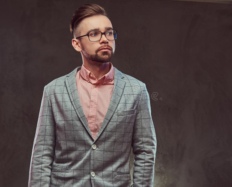 Portrait of a confident stylish bearded man with hairstyle and glasses in a gray suit and pink shirt, posing in a studio royalty free stock photos
