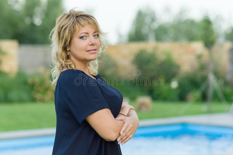 Portrait of confident successful mature woman with arms crossed. Background of pool, private residence, female looks into the came stock photography