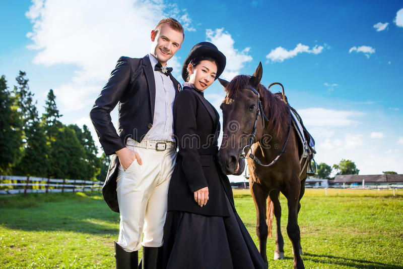 Portrait of confident well-dressed couple standing with horse on field stock image