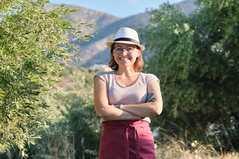 Portrait of confident woman olive farm owner, background olive trees in the mountains royalty free stock image