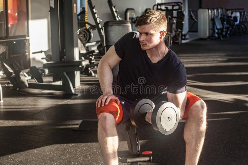 Portrait of confident young adult man handsome athlete working out in gym, sitting on a bench and holding one dumbbell with raised stock photo