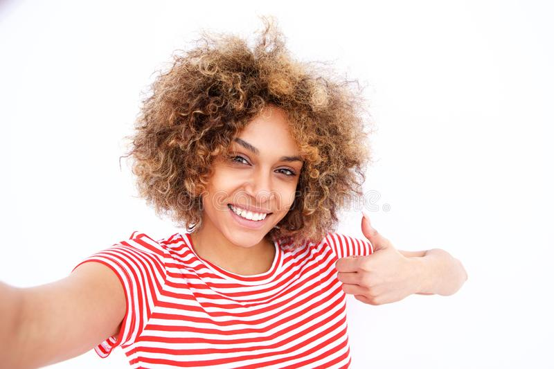 Confident young african american woman taking selfie with thumbs up. Portrait of confident young african american woman taking selfie with thumbs up against stock photography
