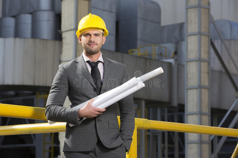 Portrait of confident young architect holding blueprints outside industry stock image