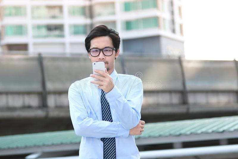 Portrait of confident young Asian business man looking mobile smart phone at outside office. stock image
