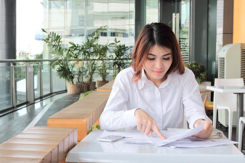 Portrait of confident young Asian business woman looking charts in her hands in office royalty free stock photo