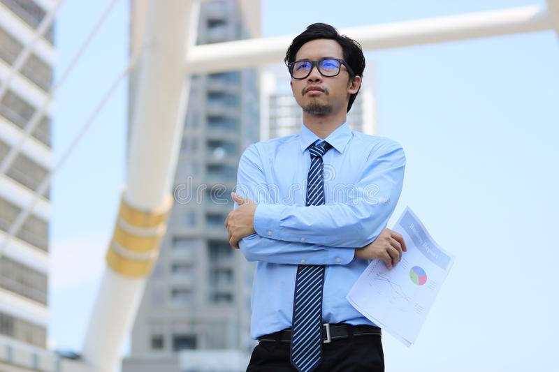 Portrait of confident young Asian businessman at urban building background. Vision business concept. stock image