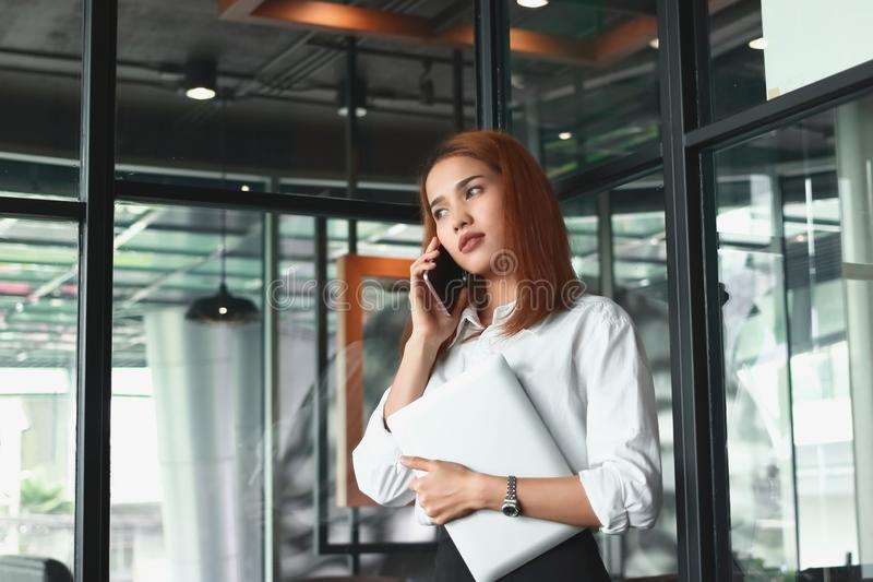 Portrait of confident young Asian businesswoman talking on phone in office. Thinking and thoughtful business concept royalty free stock photos