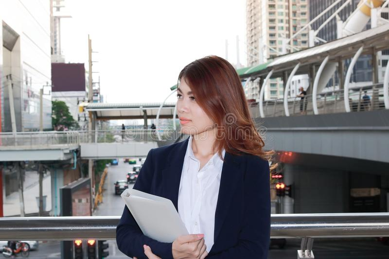Portrait of confident young Asian secretary woman with document folder standing and thinking something at city background. royalty free stock images