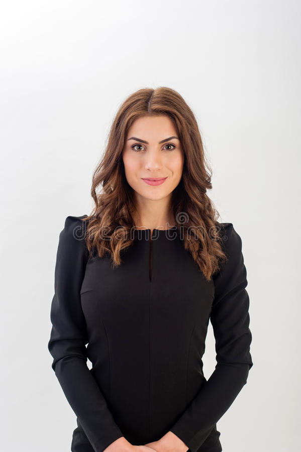 Portrait of a confident young business woman. Wearing black elegant dress and looking at camera stock image
