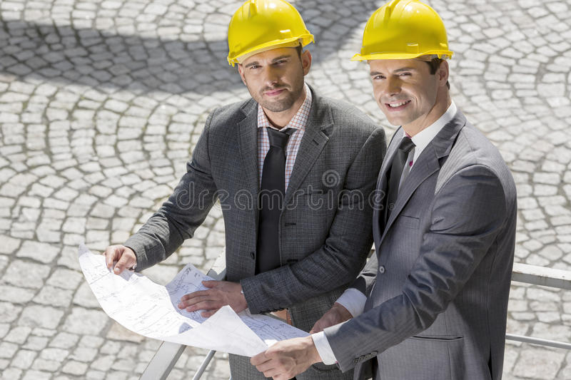 Portrait of confident young businessmen in hard hats examining blueprint outdoors royalty free stock photo