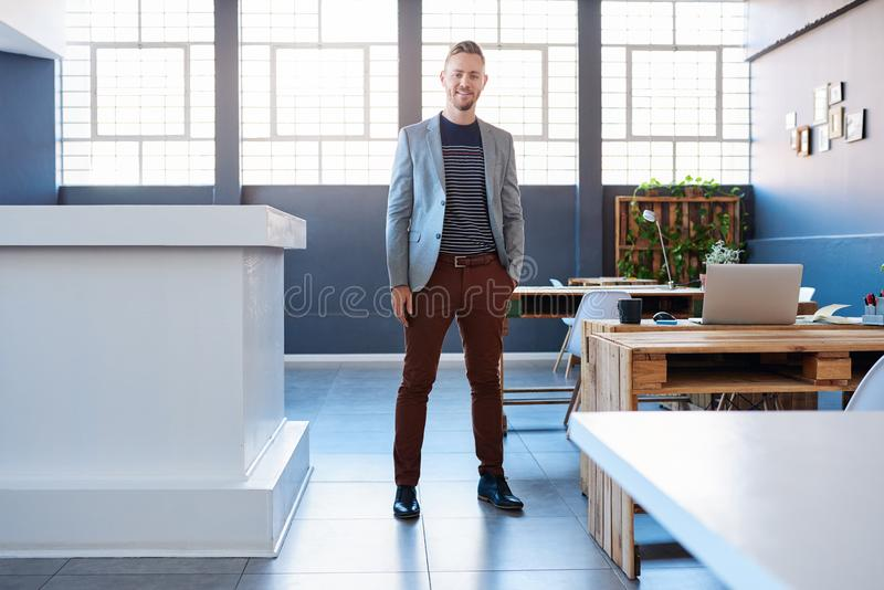 Smiling young businessman standing alone in a modern office. Portrait of a confident young entrepreneur in a blazer smiling while standing alone in a large stock images