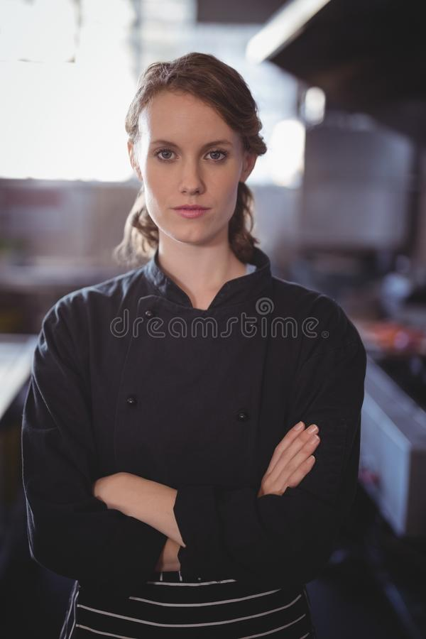 Portrait of confident young female barista standing with arms crossed. At coffee shop stock photography