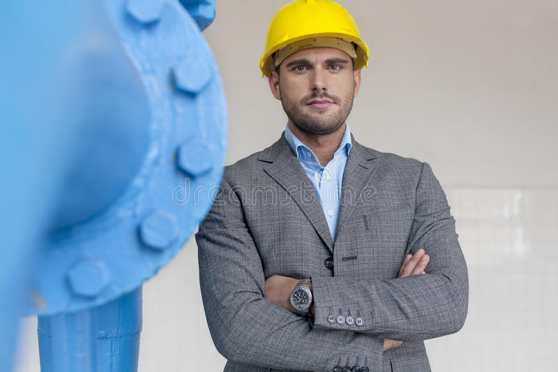 Portrait of confident young male architect standing arms crossed in industry royalty free stock images