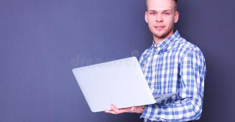 Portrait of confident young man with laptop standing over gray background. Portrait of confident young man with laptop standing over gray royalty free stock photos