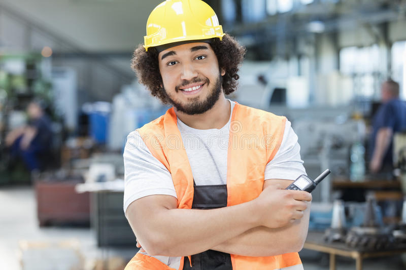 Portrait of confident young manual worker holding walkie-talkie in metal industry.  royalty free stock photography