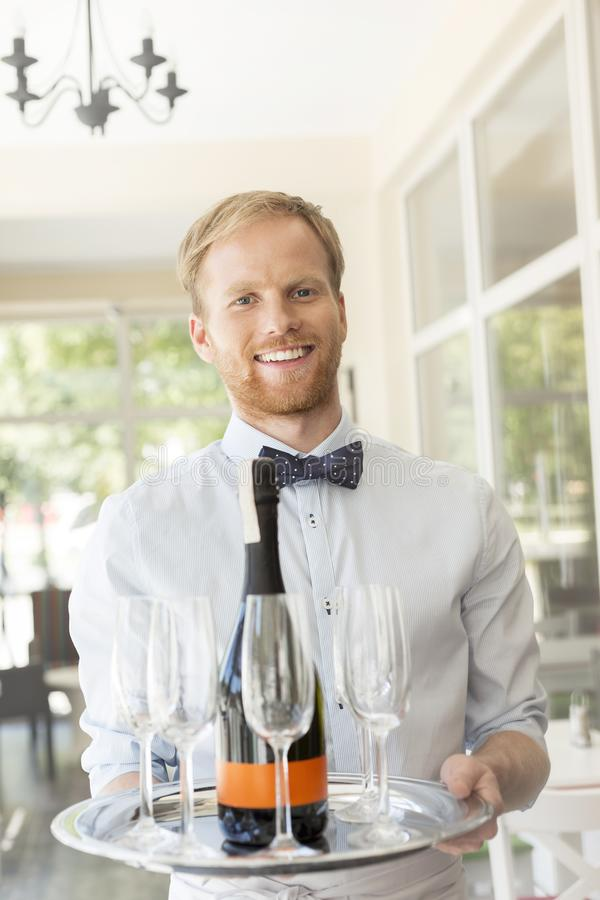 Portrait of confident young waiter serving wine at restaurant royalty free stock photos