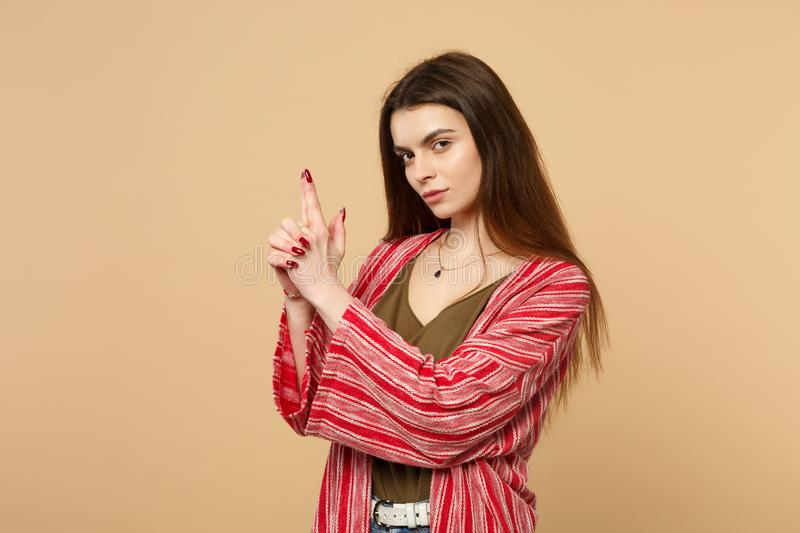 Portrait of confident young woman in casual clothes looking camera holding hands like gun isolated on pastel beige stock images