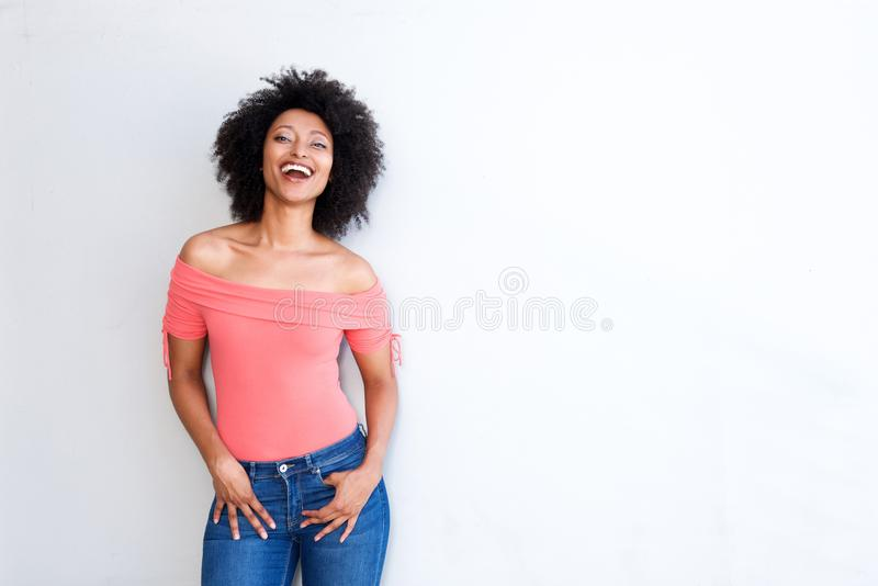Confident young woman laughing against white background with copy space royalty free stock image