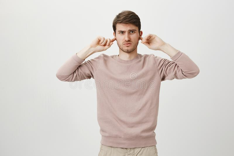 Portrait of confused and annoyed man covering ears with index fingers and looking with dislike at camera while standing. Over gray background. Guy irritated stock images