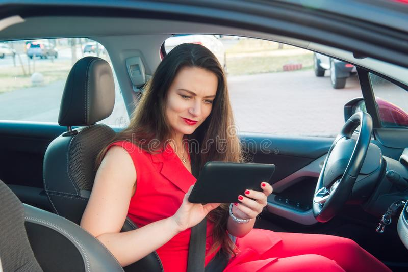Portrait of confused and anxious business lady, caucasian young woman driver in red summer suit setting up the route on a royalty free stock photography