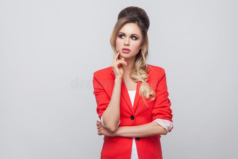 Portrait of confused beautiful business lady with hairstyle and makeup in red fancy blazer, standing, touching her face and. Thinking. indoor studio shot stock photos