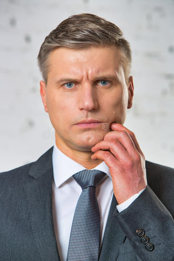 Portrait of confused businessman against brickwall royalty free stock images