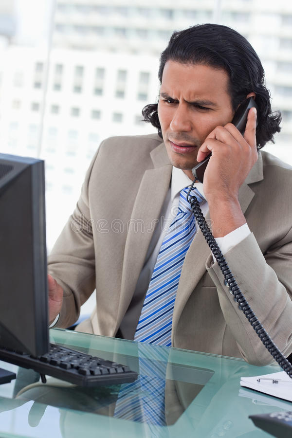 Download Portrait Of A Confused Businessman Working With A Monitor While Stock Image - Image: 22692647