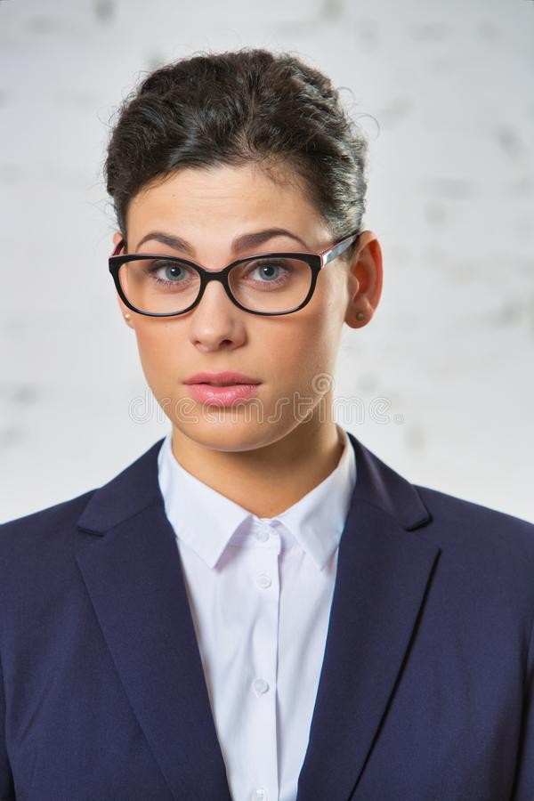 Portrait of confused businesswoman wearing eyeglasses against brickwall royalty free stock images