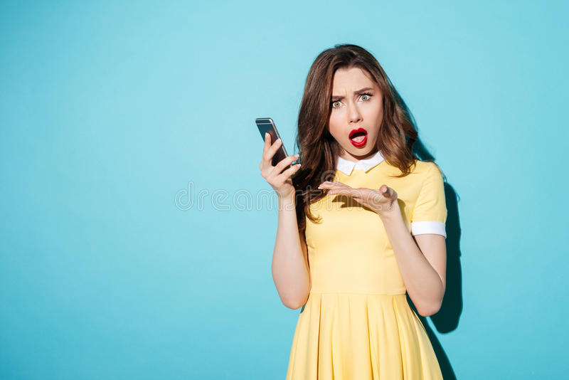 Portrait of a confused cute girl in dress pointing stock images