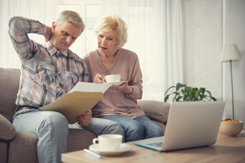 Puzzled pensioners beating their brain with bequest. Portrait of confused elderly couple focused on paper with testament. Copy space in right side royalty free stock image