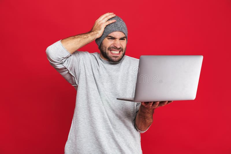 Portrait of confused guy grabbing head while holding silver laptop isolated over red background stock photos