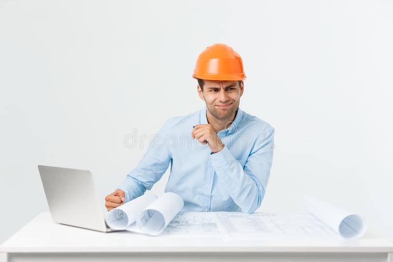 Portrait of confused male designer or architect, feels stressed, being nervous, keeps hand on head, stares in blueprint royalty free stock photography