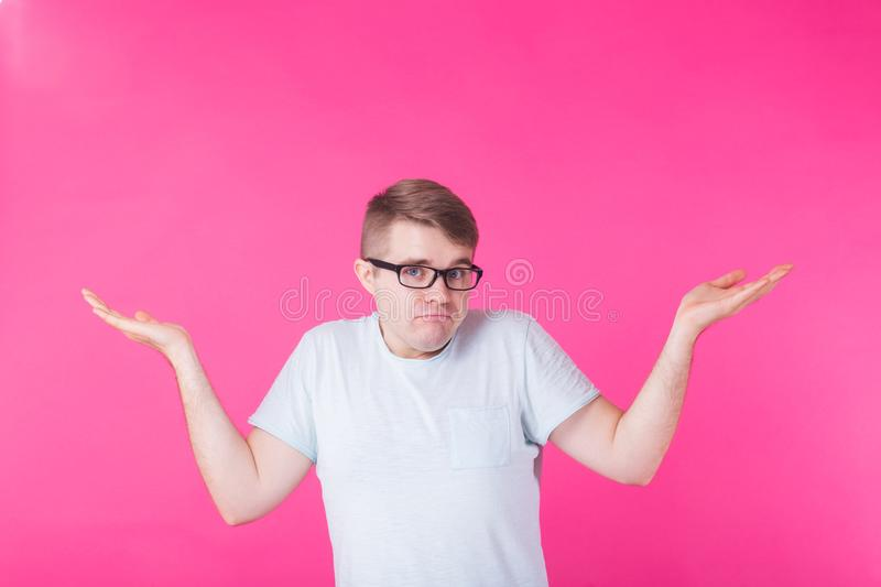 Portrait of confused man showing I don`t know gesture on pink background royalty free stock image