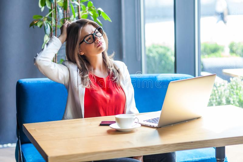 Portrait of confused query beautiful stylish brunette young woman in glasses sitting, scratching her head and thinking about new royalty free stock image