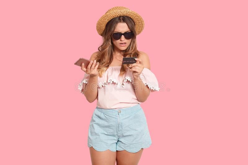 Portrait of confused shocked young female wearing summer clothes and accessories, holding smartphone and credit card in both hands stock photos