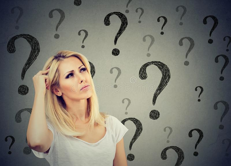 Portrait confused thinking woman bewildered scratching head seeks a solution looking up at many question marks stock image