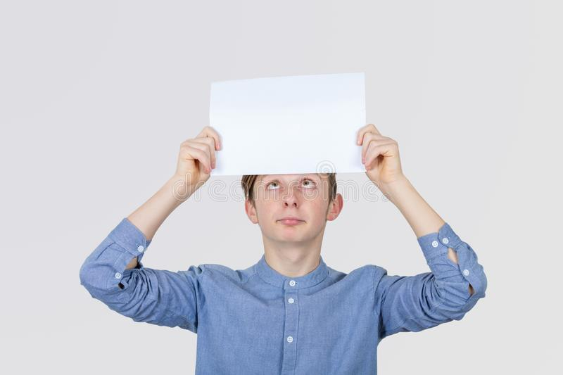 Portrait of confused, thinking young boy seeks a solution looking up, holding a paper over head gray wall background. Human face stock images