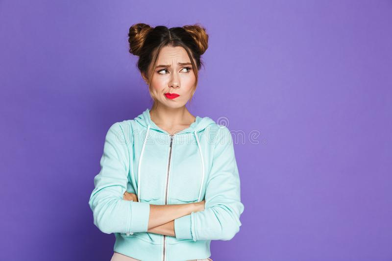 Portrait of confused woman with two buns twisting mouth and look royalty free stock photo