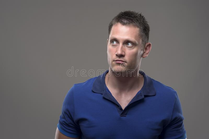 Portrait of confused young adult man looking up at copy space royalty free stock photography