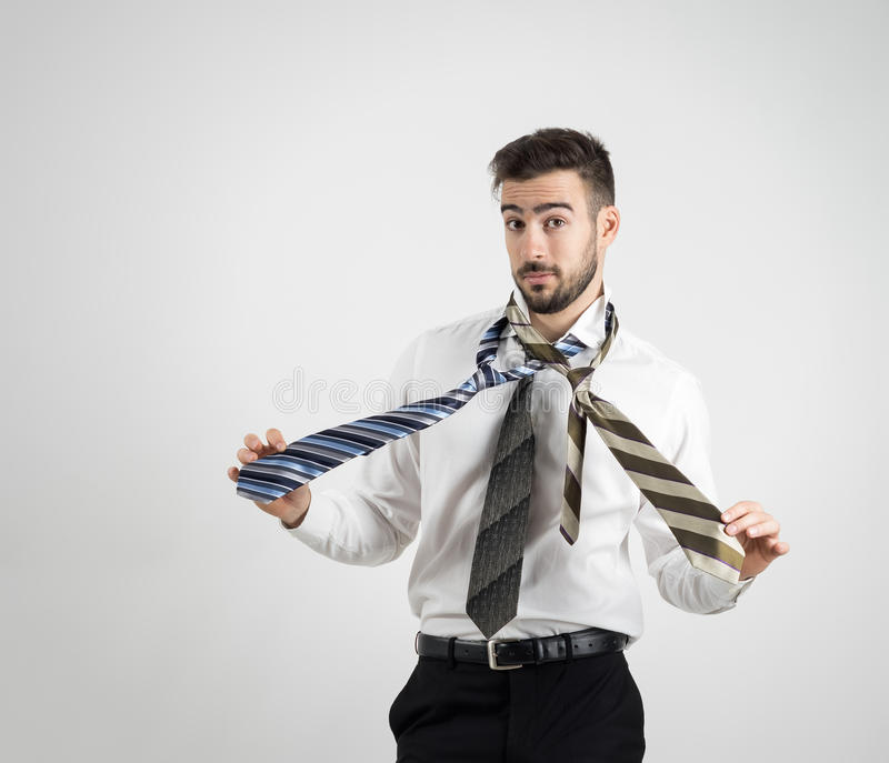 Portrait of a confused young bearded man in white shirt choosing right necktie royalty free stock photo