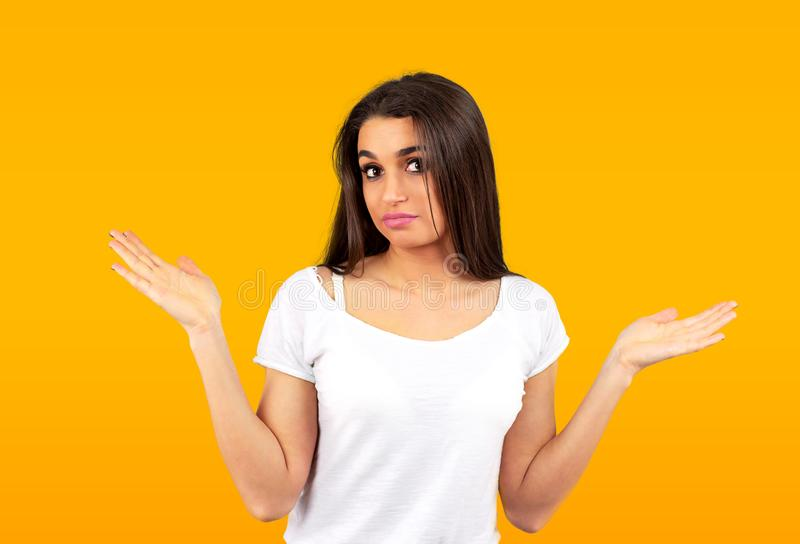 Confused young casual girl shrugging shoulders royalty free stock images