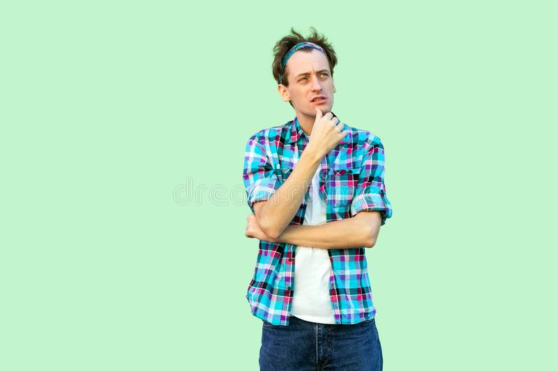 Portrait of confused young man in casual blue checkered shirt and headband standing, touching chin, thinking and concentrated to stock photo