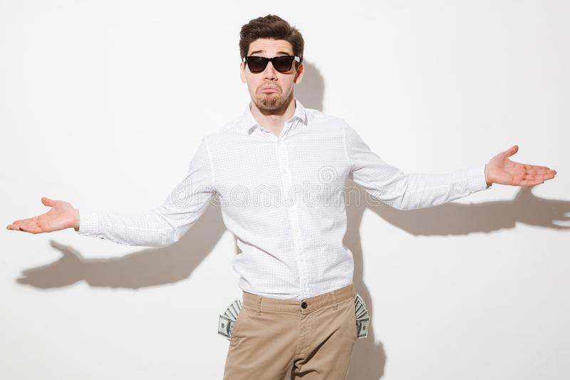 Portrait of a confused young man with money banknotes. In his pockets shrugging shoulders over white background royalty free stock images